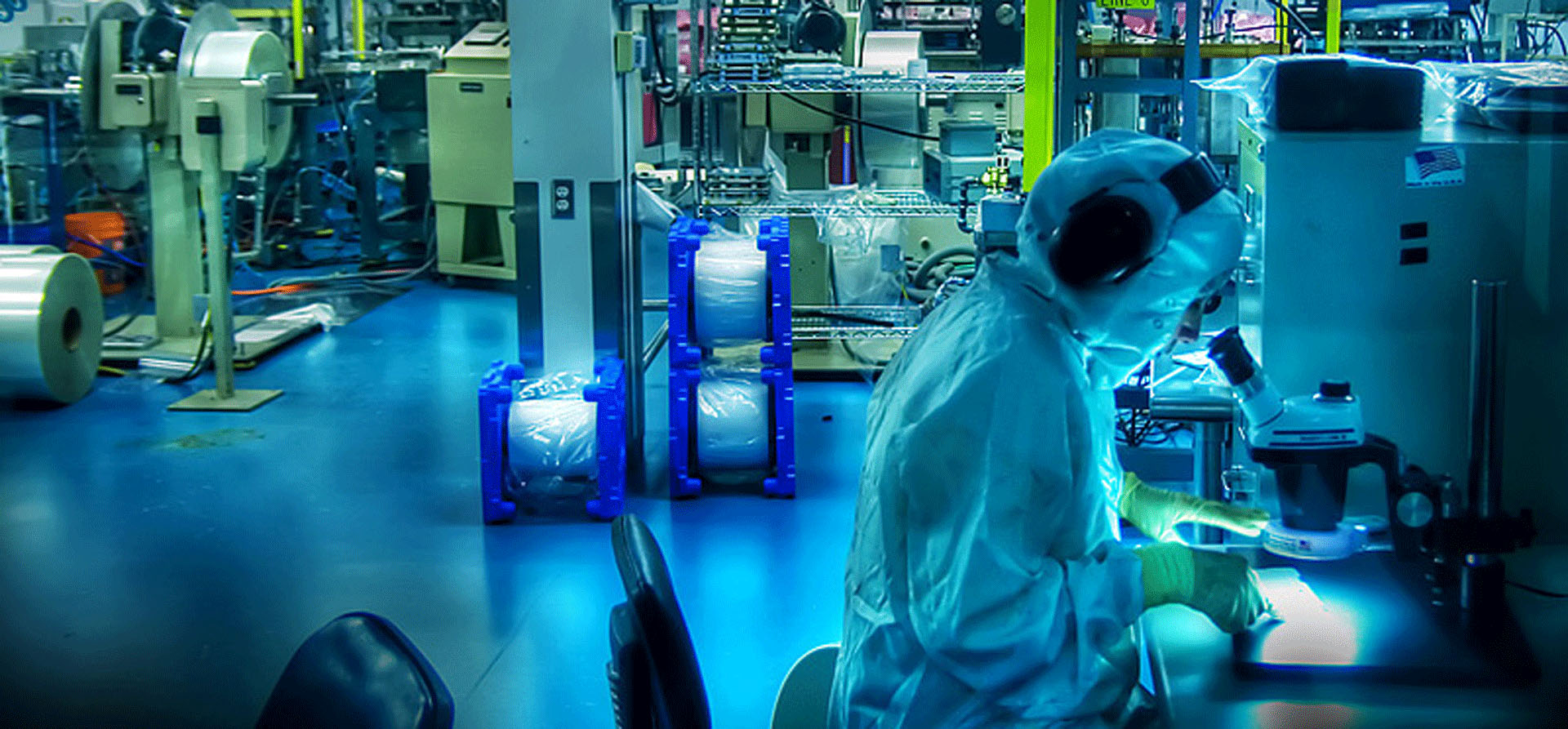 Person using microscope in an industrial setting
